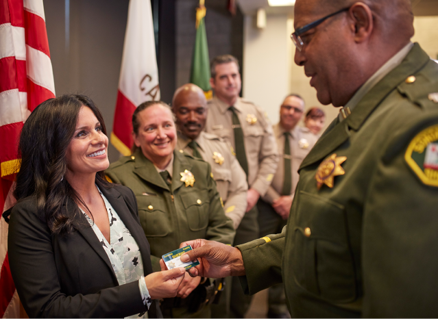 A civilian employee is given her ID badge during a swear-in ceremony.