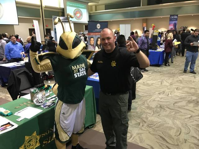 Sheriff's Office staff member poses with a mascot at a job fair.