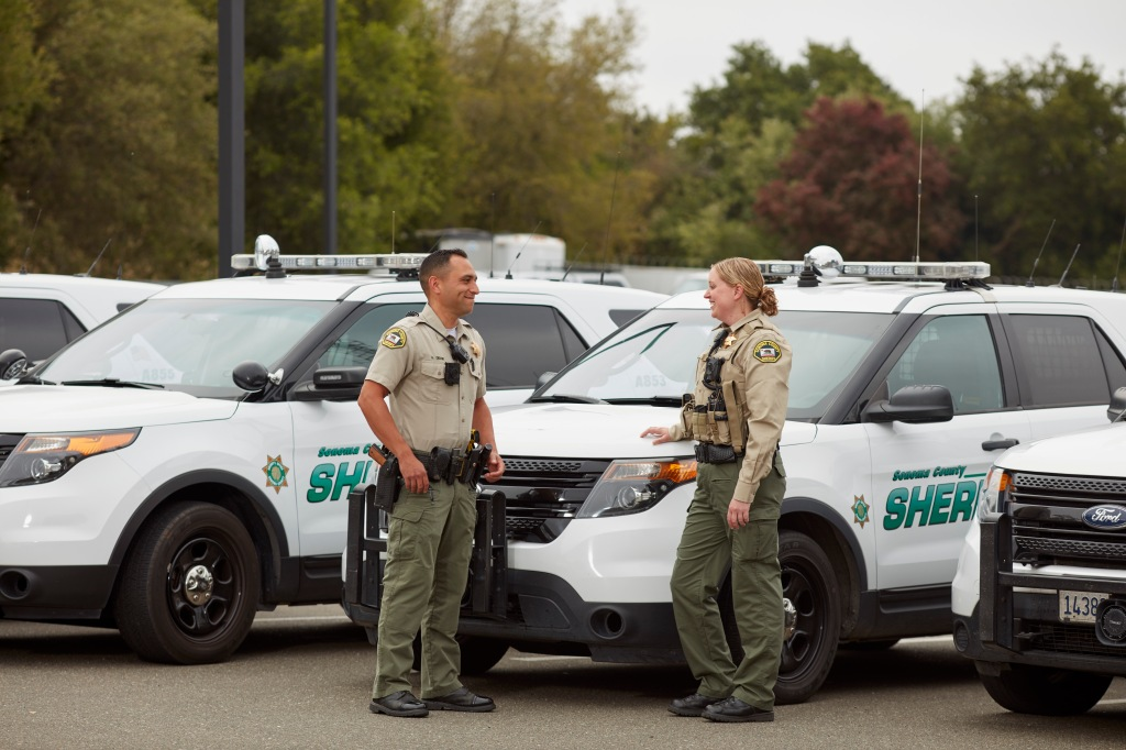 Two deputies stand next to their patrol vehicles.