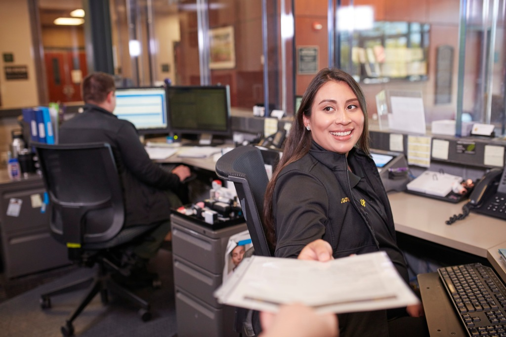 A community services officer works at the front desk of the Sheriff's Office.